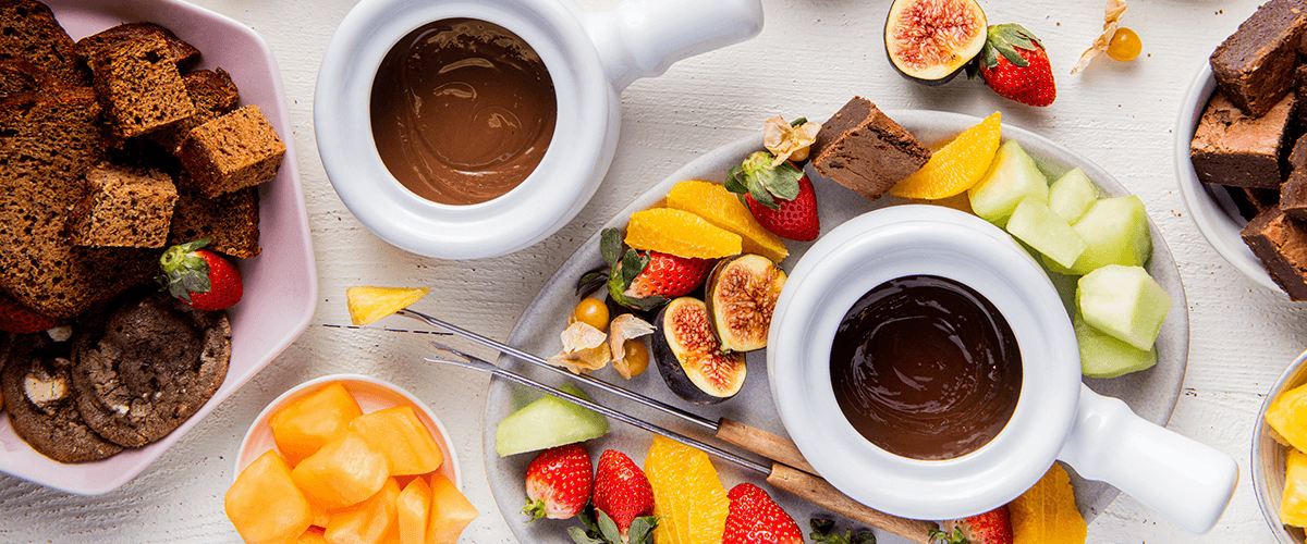Chocolate fondue spread from Goodfood featuring fondue, banana bread cubes, cookies, and fresh fruit