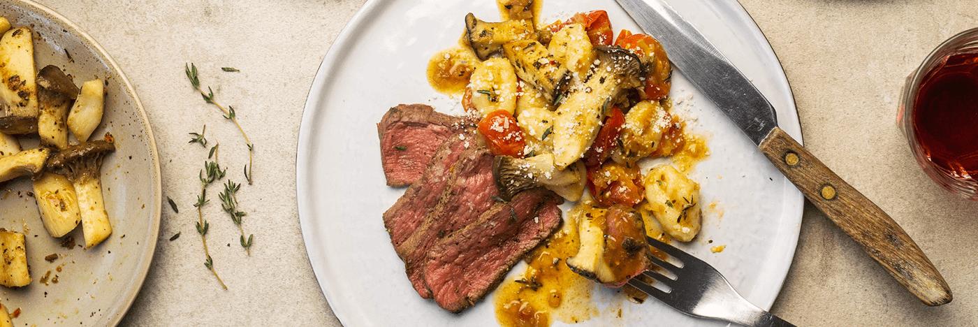 Filet mignon et gnocchi de pommes de terre frais avec tomates cerises et mini pleurotes érigés