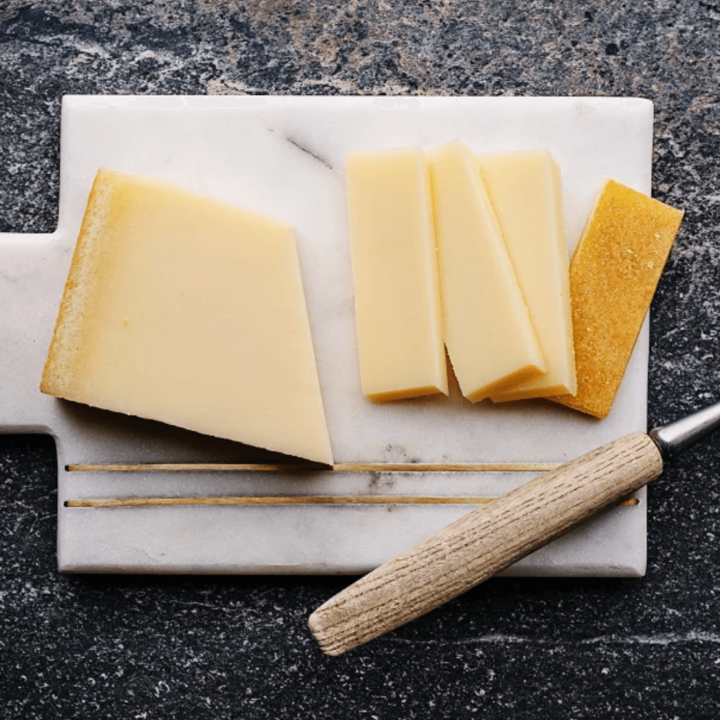 Sliced Louis d'Or cheese on a marble board
