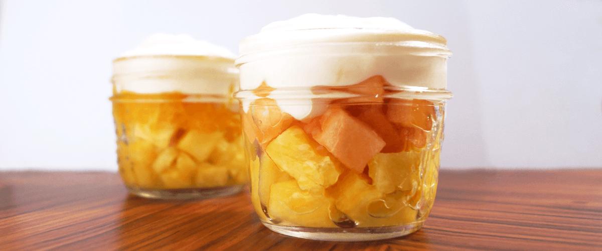 Yogurt, cantaloupe, pineapple parfait that has the colours of candy corn