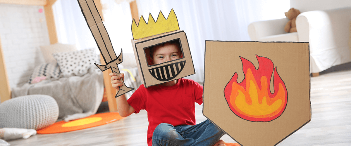 A young boy plays with his cardboard knight costume in his bedroom.