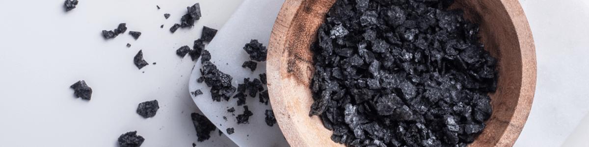 Bol en bois avec du sel noir et du sel noir saupoudré à gauche