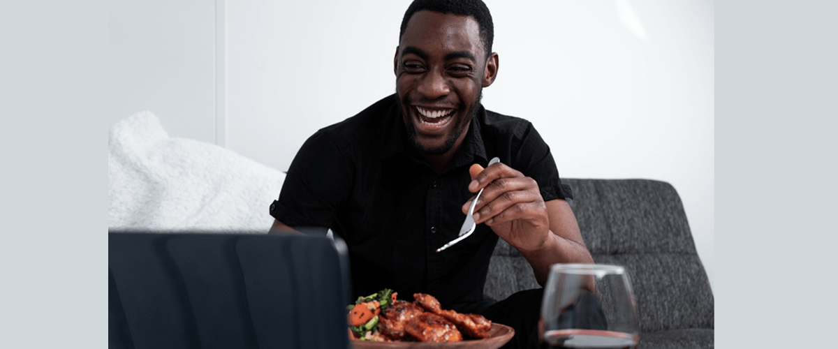 Mike Regis eating a Goodfood dinner in front of a tablet while laughing with friends on screen