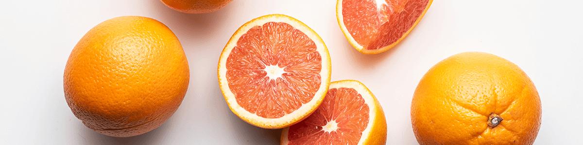 Image of whole and cut cara cara oranges