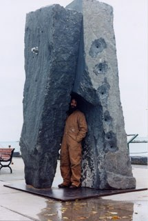 Photo of Harry Gordon and his work <em>Passage</em>, 2001. Black granite. 11 x 8 x 5 feet. Photo taken at Governor's State, University Park, IL. Image courtesy of the artist.