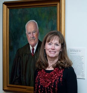 Barbara Lewis in front of her portrait of Hon. John Fullam at the Michener Art Museum, 2014.