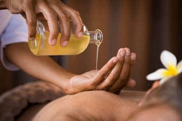 Therapist pouring massage oil spa