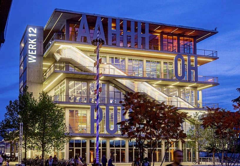 """<p>Das Werksviertel im Münchner Ostbahnhof hat einen neuen Partyraum. Für die oberste Etage gibt es einen besonderen Plan: Ein Privatmann will eine riesige Party-Wohnung einrichten</p><p><br></p><p>München - AAHHH, PUH, HIHI, WOW – das neue Gebäude namens Werk12 im Werksviertel am Ostbahnhof ist ein echter Hingucker.Die Fassade hat jedoch viel mehr als eine Comic-Sprache. Im vierten Stock mit sensationellem Blick auf die Stadt wurde am Donnerstagabend die Einweihung eines ungewöhnlichen Neubaus gefeiert.</p><p><br></p><p>Auch in Zukunft sollte es eine Party geben. Wie Eigentümer und Investor Werner Eckart auf Nachfrage erzählte, will """"ein Privatmann dort eine riesige Party-Wohnung einrichten"""". Es werden keine zusätzlichen Informationen über den Preis oder die Größe des Kaufs veröffentlicht.</p><p><br></p><p><em>Werk12 am Ostbahnhof: Neues Zuhause für Klubs und Fitnesscenter</em></p><p><br></p><p>Im Erdgeschoss gibt es drei öffentliche Clubflächen. Die """"Gin City"""" hat schon eröffnet, im Dezember soll der """"Schlagergarten"""" einziehen. Obendrüber erstreckt sich auf drei Etagen das Fitnesscenter """"body+soul"""", in dem es unter anderem einen 25 Meter langen Swimmingpool gibt.</p><p><br></p><p>Der Entwurf des Neubaus stammt vom Architekturbüro MVRDV aus Rotterdam, das als eines der erfolgreichsten niederländischen Architekturbüros gilt. Begeistert vom Holland-Pavillon auf der Hannover-Expo 2013, holte Eckart sie in sein Viertel. New Factory 12 ist von diesem Pavillon mit zwei vollständig verglasten Räumen und umlaufenden Balkonen inspiriert, die mehr als drei Meter tief sind. Eine weitere Besonderheit ist die außenliegende Erschließung.&nbsp;</p><p><br></p><p><em>Fassade des Werk12: Eine Hommage an Graffiti-Kultur</em></p><p><br></p><p>Das i-Tüpfelchen ist jedoch die Gestaltung der Fassade. Das Konzept für die rund fünf Meter hohen Buchstaben stammt von den Münchner Künstlern Beate Engl und Christian Englmann. In Anlehnung an die Comic-Sprache werden Emotionen und Äußerungen da"""