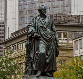 """<p>Der noble Gasthof Weidenbusch im Steinweg war stadtbekannt für rauschende Feste und Konzerte berühmter Künstler im großen Speisesaal mit mehr als 1000 Plätzen. Vor 200 Jahren, am 28. August 1819, traf sich das berühmte Unternehmen auf Einladung des Frankfurter Bankiers Johann Jacob Willemer in Weidenbush, um Johann Wolfgang von Goethe an dessen 70. Geburtstag gebührend zu würdigen. Das Jubiläum selbst nahm die Einladung seines Freundes Willemer nicht an, da der Dichter an großen Geburtstagsfeiern fast nicht teilnahm. Im Gegenteil, am Vorabend seiner Gefährten in Weimar erholte er sich und ging an seinem Geburtstag zur Behandlung nach Karlsbad.</p><p><br></p><p><em>Goethe-Denkmal in Frankfurt: Bankier scheiterte mit Spendengesuch</em></p><p><br></p><p>Im Gasthof Weidenbusch wurden an jenem Samstag Pläne für eine großzügige Tempelanlage zu Ehren Goethes auf einer kleinen Maininsel am Schneidwall (heutiges Nizza) vorgestellt. Der Bankier Simon Moritz von Betman übernahm die Aufgabe, Spenden für den Rundtempel zu sammeln, dessen Kosten auf rund 50.000 Gulden geschätzt wurden. Diese Idee ist aber kläglich gescheitert, weil nur wenig Geld eingesammelt wurde.</p><p><br></p><p>Es kam dann doch noch, allerdings erst nach Goethes Tod - er starb am 22. März 1832 in seiner Wahlheimat Weimar im Alter von 82 Jahren. Fünf Jahre später nahmen Frankfurter Bürger einen neuen Anlauf für ein Goethedenkmal. Als 1841 von den veranschlagten Kosten in Höhe von 53 000 Gulden mehr als die Hälfte gesammelt worden war, erhielt der Münchner Bildhauer Ludwig von Schwanthaler (1802-1848), """"Hofkünstler"""" von Bayernkönig Ludwig I., den Auftrag. Schwanthalers bedeutendstes Werk ist die berühmte Bavaria an der Theresienwiese, ein Wahrzeichen Münchens. Fast 19 Meter hoch und 87 Tonnen schwer ist die dort 1850 enthüllte Personifizierung Bayerns.</p><p><br></p><p><em>Frankfurts Goethe ist 6,90 Meter hoch und knapp sieben Tonnen schwer</em></p><p><br></p><p>Schwanthaler schuf Goethes Frankfurter Skulpt"""