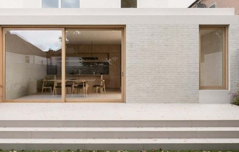"""<p>Architecture practice Thomas-McBrien enlarged a London house by attaching a utility room that is hidden behind a secret door along with dining space and kitchen and an oak-lined reading nook.</p><p>The studio said, to produce a """"calm and relaxing"""" space, lightly washed oak joinery and pale, mortar-washed bricks were used.</p><p>This project involves a site that is inclined down a total of 1.2 meters in the direction of the rear garden.</p><p>Building a split-level floor plan comes as an advantage of this extension's design by stepping down from the main house.</p><p>This extension is one and a half floors underneath the existing ground floor, which runs along the full width of the existing property.</p><p>A wood-framed sliding door in the extension adds to a terrace, which is made by a set of wide, white steps that runs along the entire length.&nbsp;</p><p>The new extension also implements a utility and storage room that is hidden behind a deep, timber-lined partition, in addition to the kitchen and dining area.</p><p>This concealed room is entered via a hidden door that completely blends in with the wooden wall finishes.</p><p>This partition also duplicates a seating alcove, which creates a window seat overlooking the garden.</p><p><br></p>"""