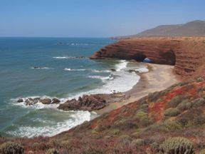 "<p><strong style=""color: rgb(161, 0, 0);""><em>Located on the southwestern coast of Morocco, the secluded Legzira Beach is hidden under the arches of orange-red cliffs. A kilometer-long section of the picturesque coast, where you can meet perhaps only surfers and local fishermen, is a place where people come for expressive landscapes. The stone arches towering over a deserted beach have been formed for thousands of years by sea currents, tides. The rocky cliffs surrounding Legzira, in the rays of the setting sun, acquire saturated orange and terracotta colors, casting with metallic shades of the blue reflected from the ocean.</em></strong></p>"