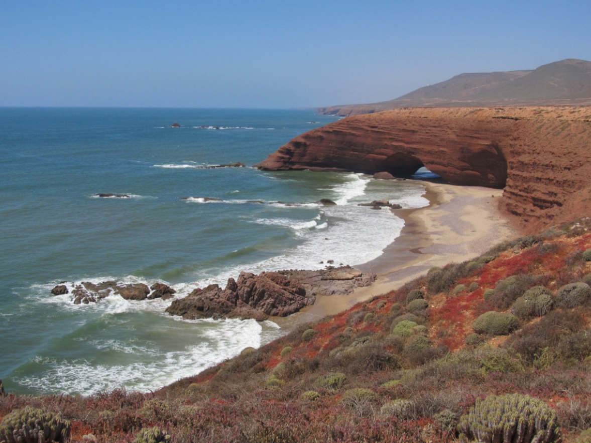 """<p><strong style=""""color: rgb(161, 0, 0);""""><em>Located on the southwestern coast of Morocco, the secluded Legzira Beach is hidden under the arches of orange-red cliffs. A kilometer-long section of the picturesque coast, where you can meet perhaps only surfers and local fishermen, is a place where people come for expressive landscapes. The stone arches towering over a deserted beach have been formed for thousands of years by sea currents, tides. The rocky cliffs surrounding Legzira, in the rays of the setting sun, acquire saturated orange and terracotta colors, casting with metallic shades of the blue reflected from the ocean.</em></strong></p>"""