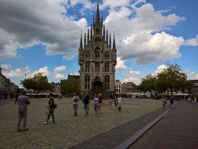 """<p><span style=""""color: rgb(0, 0, 0);"""">Гауда — это не только вкусный сыр, но и прекрасный город. Главное здание на площади — ратуша. Она считается одной из самых красивых ратуш не только Голландии, но и Европы. Она действительно потрясающе красива и напоминает сказочный замок своим обильно декорированным башенками, зубчиками и шпилёчками фасадом. Строительство этого здания началось в 1448 году, после того, как город оправился от очередного пожара, уничтожившего его большую часть. Строительство длилось 11 лет. Вплоть до 17 столетия постройку окружал ров, и единственной возможностью попасть внутрь был подъемный мост. В XVII веке к ратуше была пристроена лестница, ведущая в само здание и на балкон на заднем фасаде, который использовался и как эшафот. Дверь из здания на балкон появилась только в 1897 году, когда королева Вильгельмина должна была приветствовать народ с балкона ратуши. По сложившейся традиции, преступник, признанный виновным, покидал здание по левой лестнице и следовал на балкон, огибая здание; признанные невиновными выходили из ратуши по правой лестнице. До сих пор молодоженам, заключающим брак в старой ратуше, настоятельно советуют выходить из здания по правой лестнице.</span></p>"""