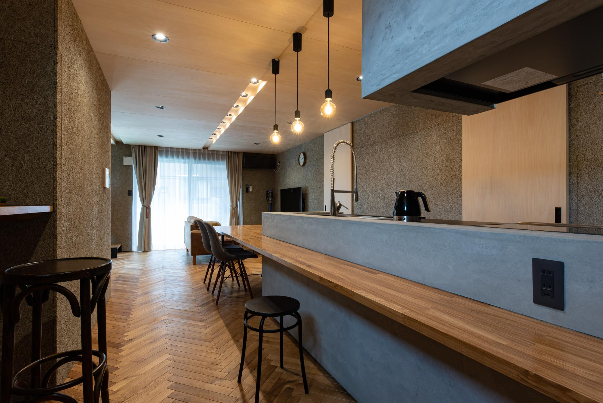 キッチンはクリナップ製CENTRO対面式アイランド型セラミックトップ。キッチン周りはモルタル仕上げにし、ダイニングテーブル及びカウンターをキッチンと一体化するように造作。