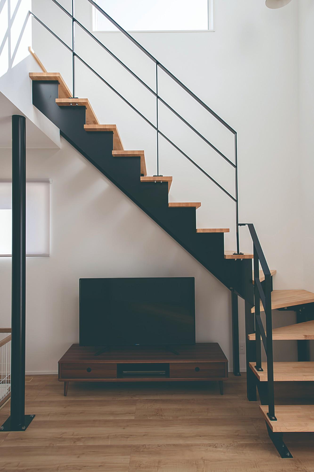 スタイリッシュな鉄骨階段。アイアンの黒が優しい色調のリビングを引き締めている。