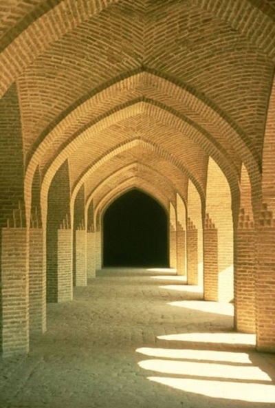 A picture of an outdoor walkway covered by brick arches.