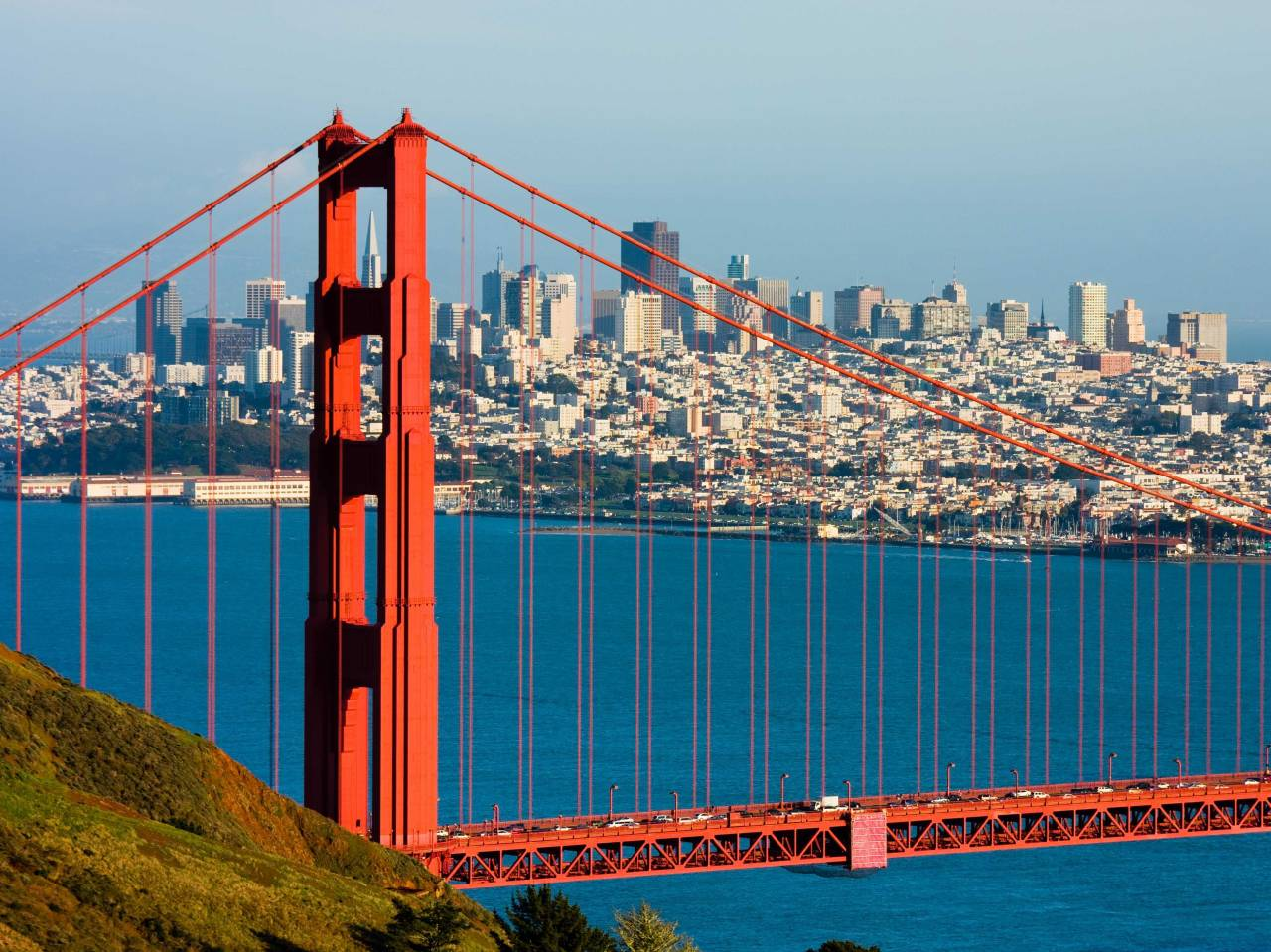 A picture of the Golden Gate Bridge during the day. San Francisco can be seen in the background