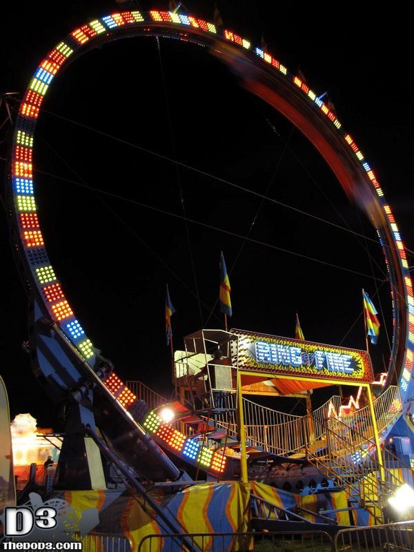 A picture of a large amusement park ride called the ring of fire. It is a roller coaster track in the shape of a large vertical ring.