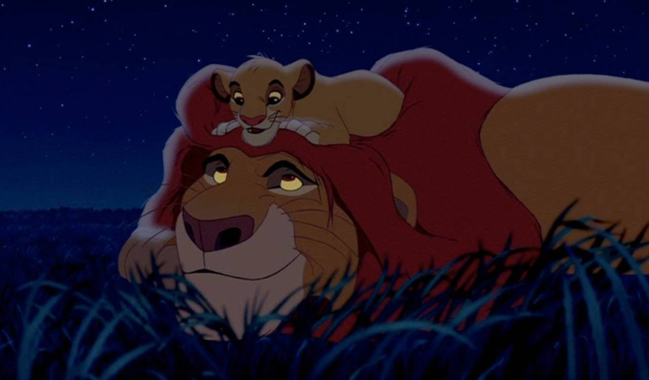 A picture of Simba and Mufasa, two lions from The lion King. The baby tiger Simba is resting on the adult tiger, Mufasa's head.