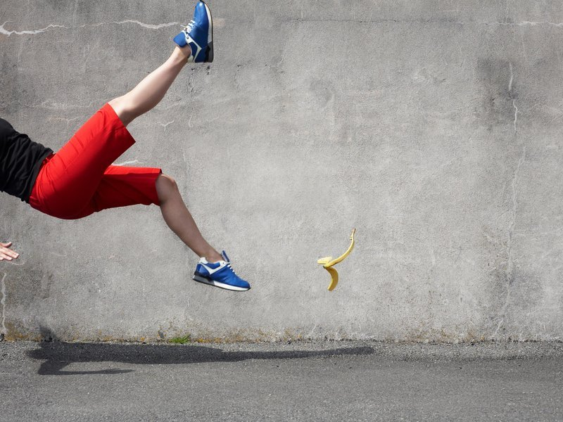 A picture of a person slipping on a banana peel. Only the person's lower body can be seen frozen in midfall. All of this is before a grey wall.