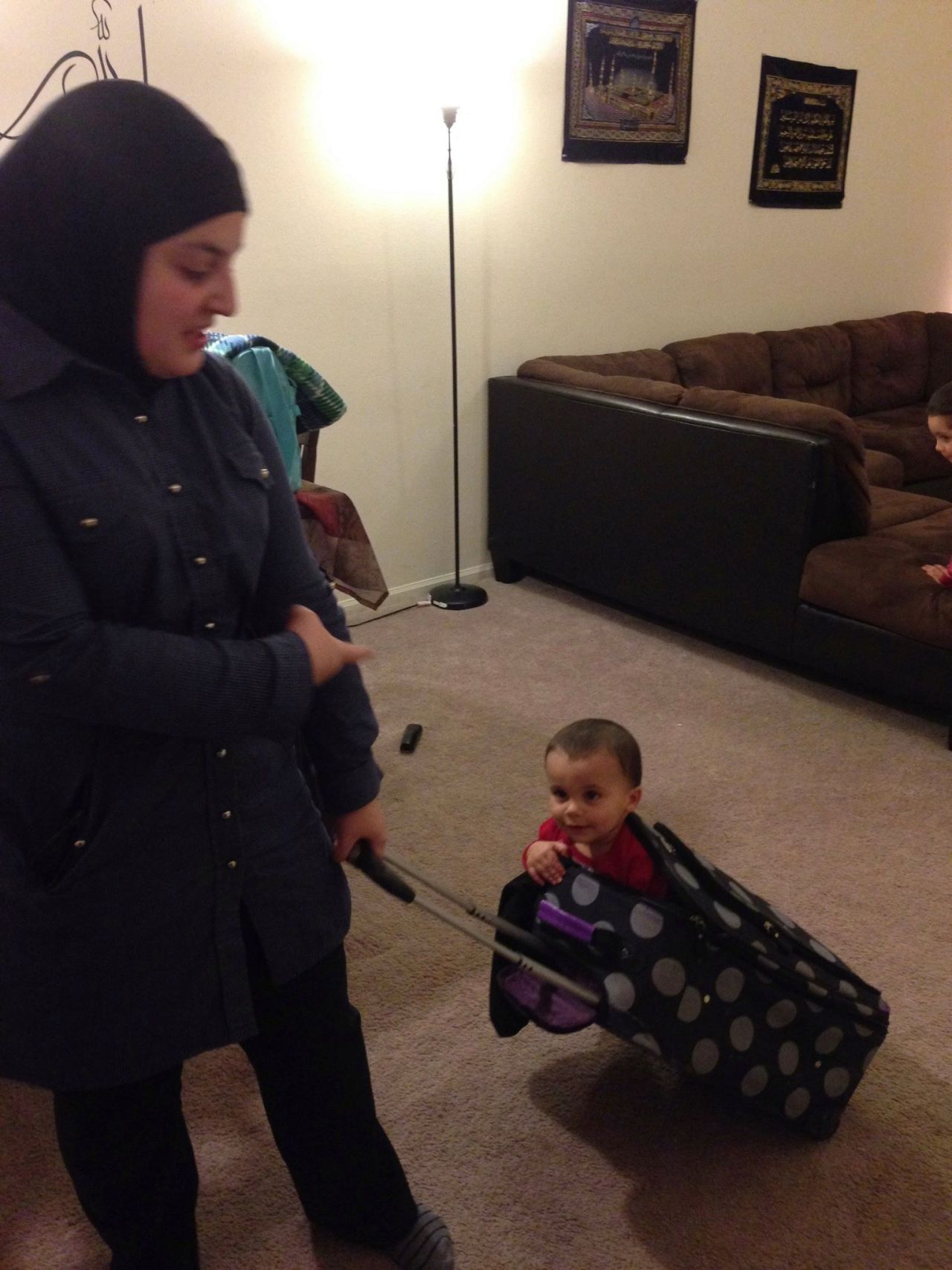 Mona pulling a black and grey luggage bag with a toddler inside it.