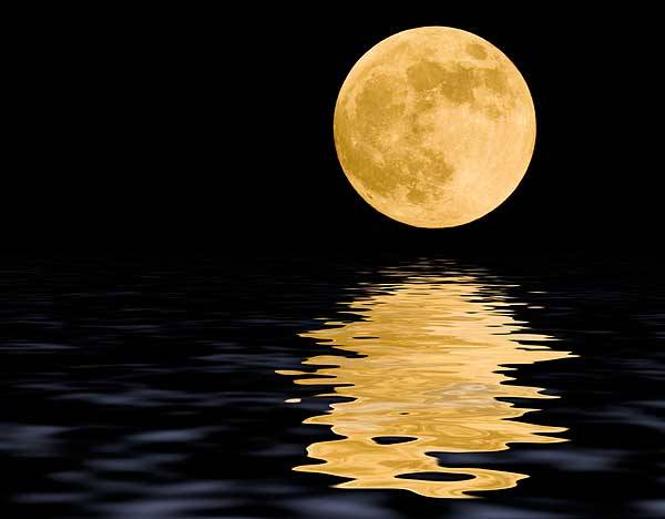 A bright pale yellow full moon reflecting into a body of water underneath.