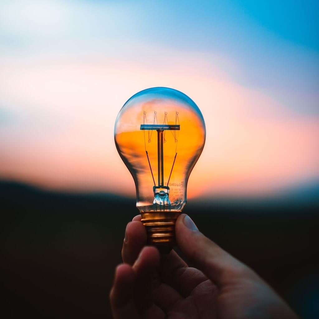 A hand holding a standard lightbulb before a sunset sky. The sunset sky can be seen through the lightbulb