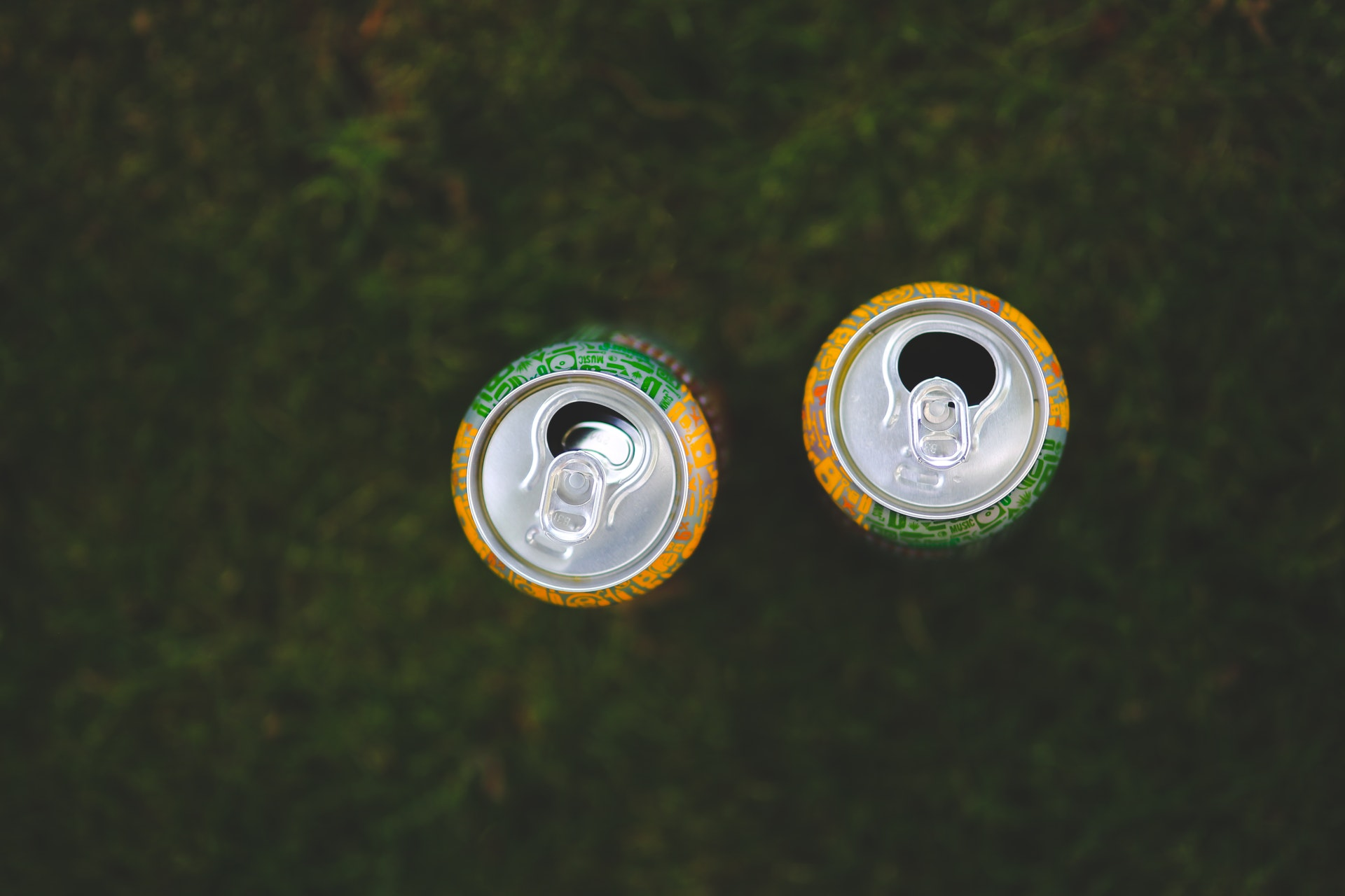 An overhead image of two open soda cans on a grass floor.