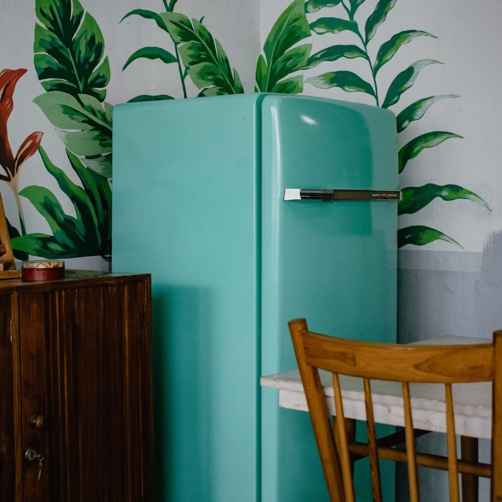 An image of a cyan fridge in a kitchen. Right before the fridge is a small table with a wooden chair. Green plants can also be seen behind the fridge.