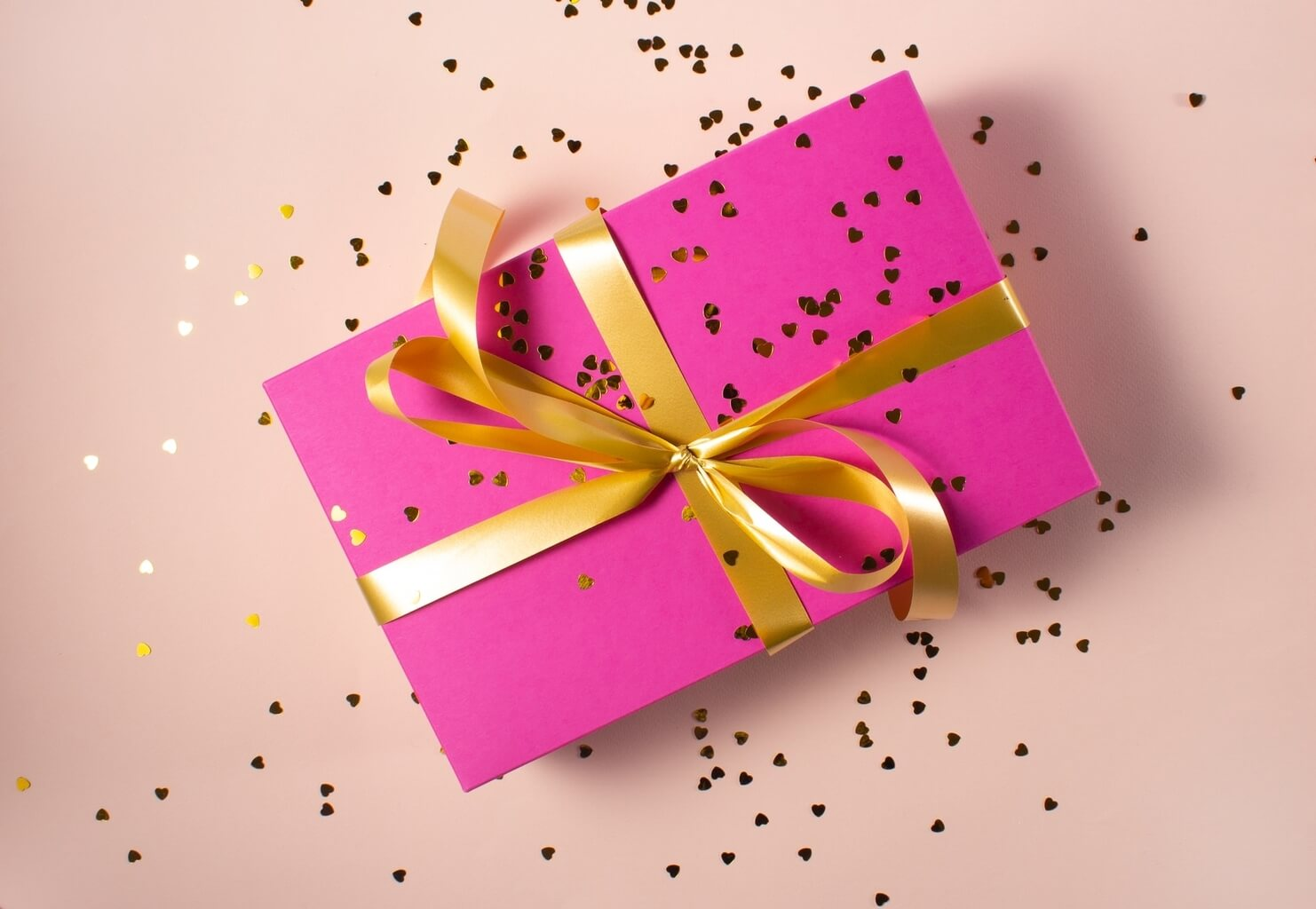 A picture of a ping gift box viewed from overhead. It is wrapped with a gold ribbon and gold confetti is scattered on and around the box.