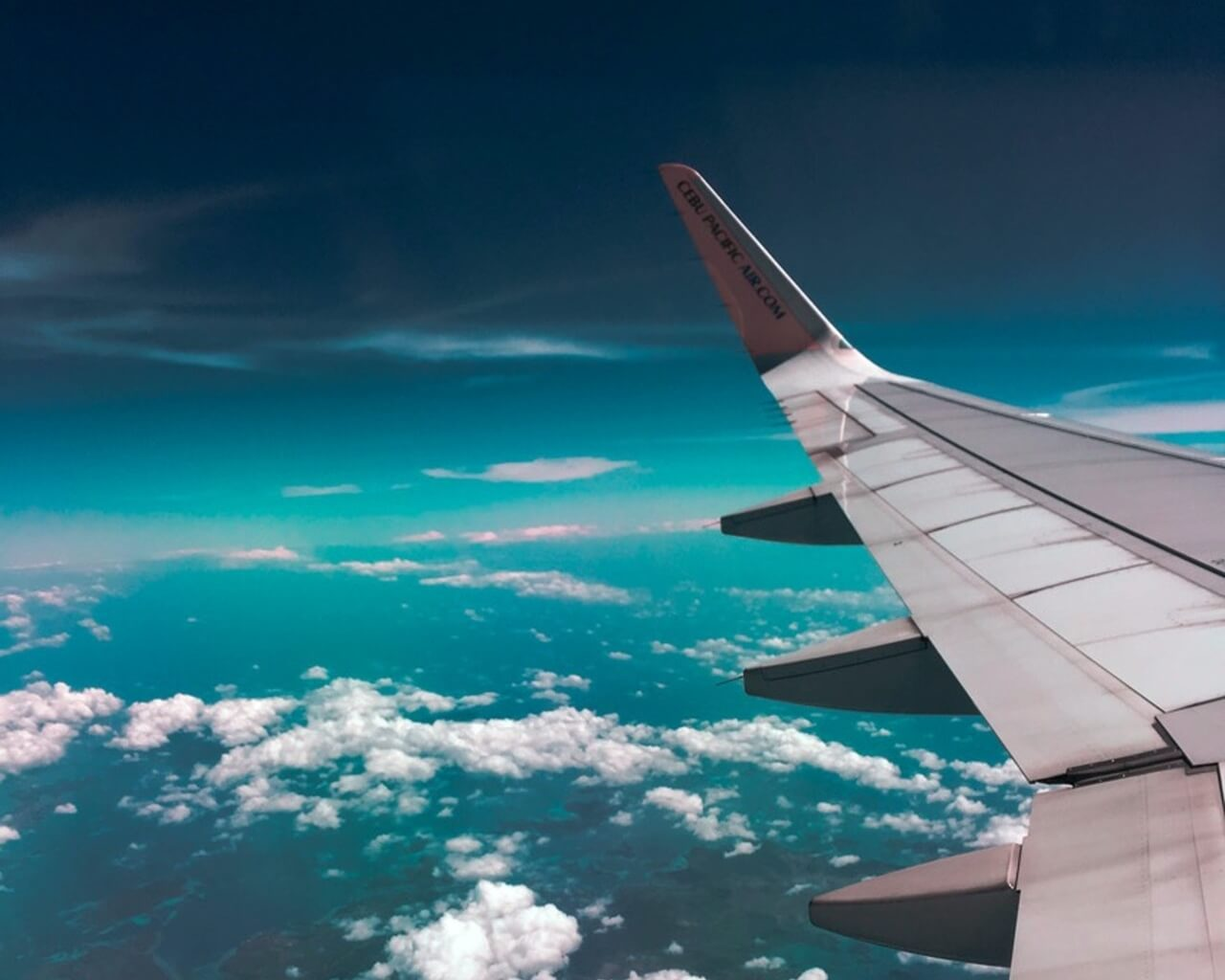A picture of a plane wing high in the sky above a blue ocean.