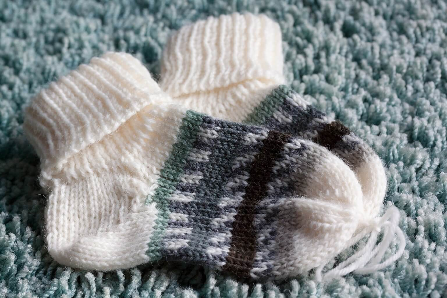 A picture of two small wool baby socks.