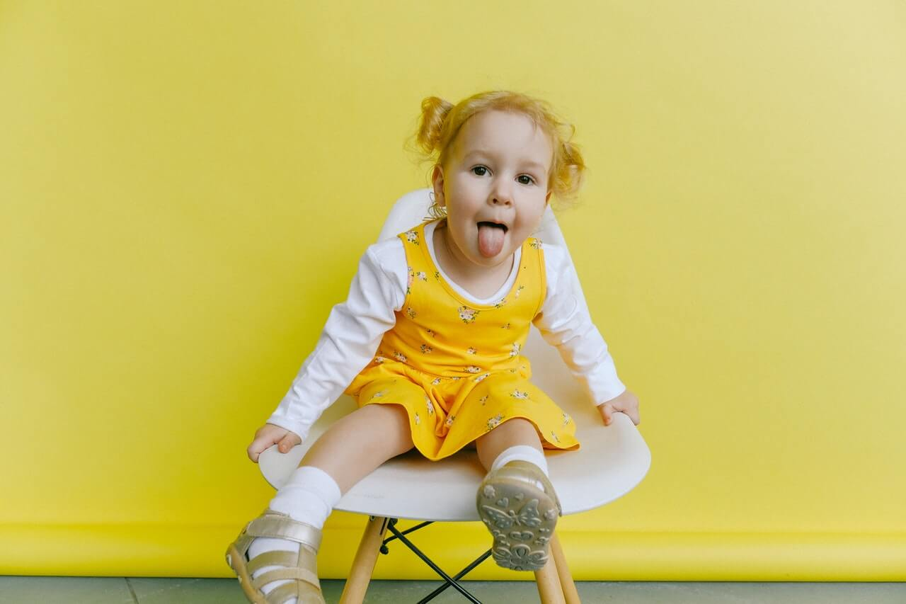 A picture of a toddler sitting on a white chair in front of a yellow background. The toddler is blond and is wearing a yellow and white dress.
