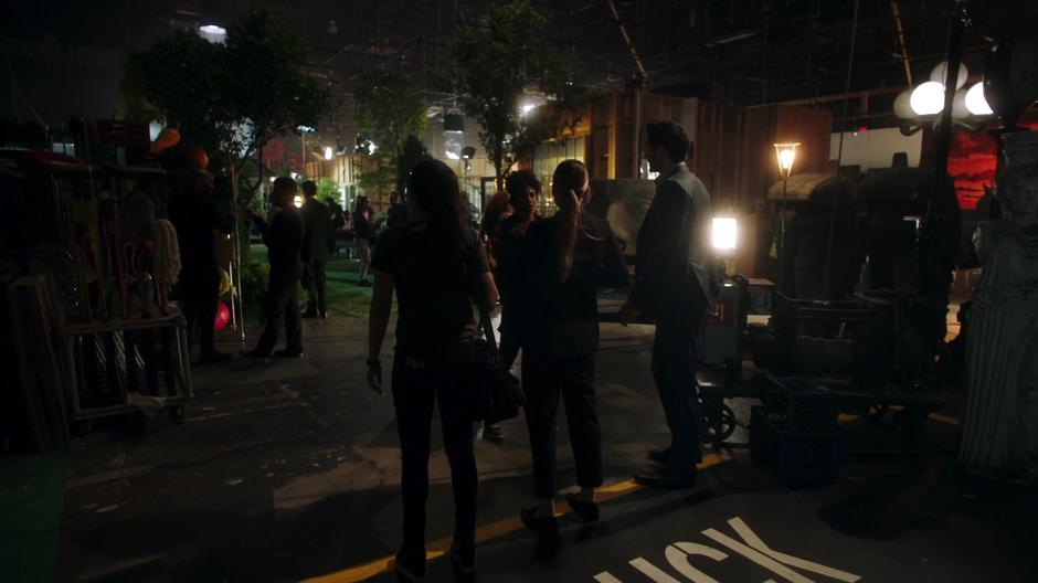 Ella, Chloe, and Lucifer get stopped by a PA at the door of the sound stage.