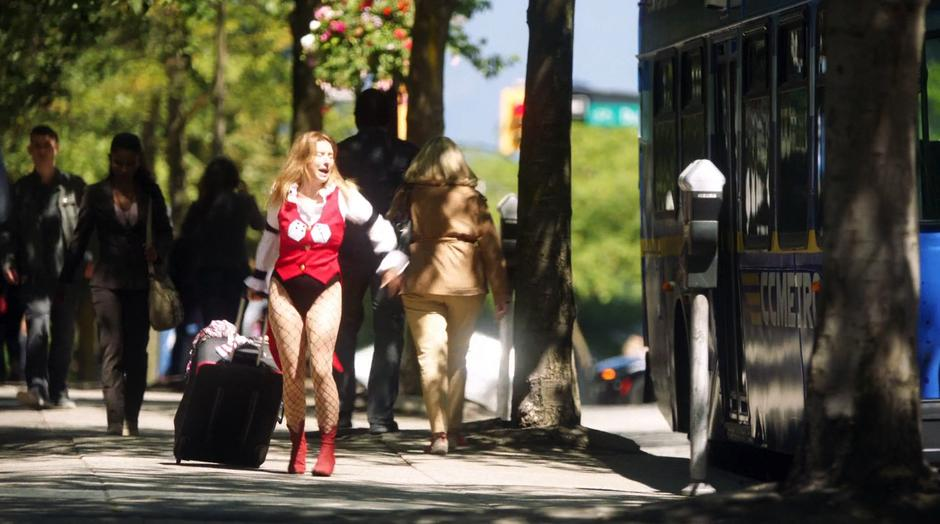 Rebecca Sharpe rushes down the street towards the bus while dragging her big suitcase.
