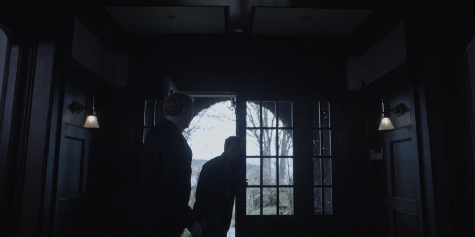 A guard holds the door open for Grant as he enter the mansion.