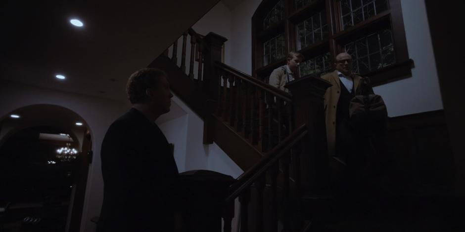 Vincent comes down the stairs with his son and tells one of his guards that they are leaving for good.