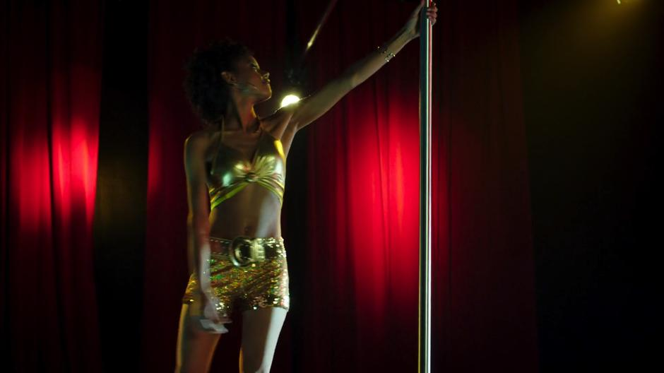 Joanie comes out on stage in the skimpy outfit to do a pole dance.