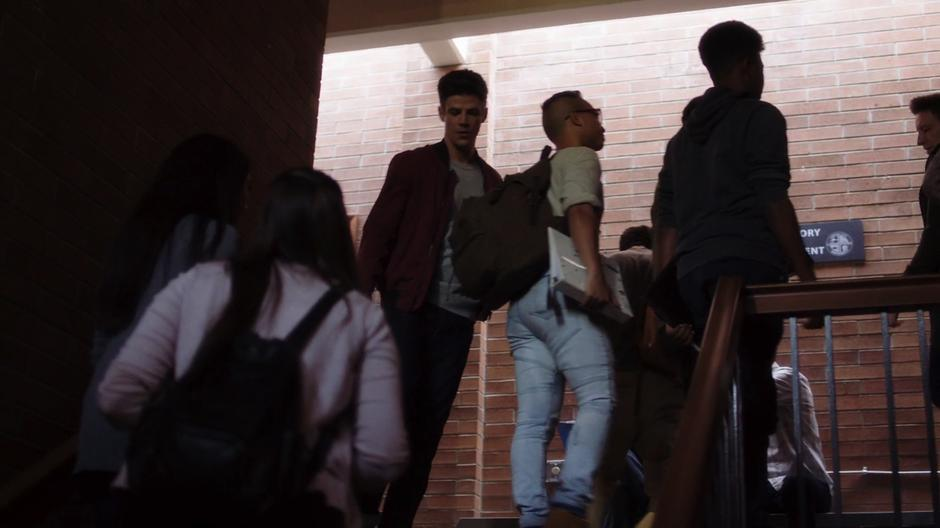 Barry walks through the flow of students towards the stairs.