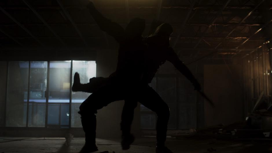 Oliver fights a ninja in an empty building.