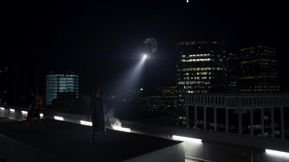 Kara lands on the roof where Reign is waiting while a helicopter circles around.