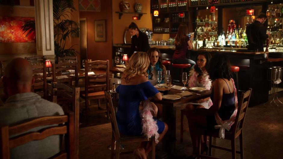 Felicity, Caitlin, Cecile, and Iris sit at the table for the bachelorette party.