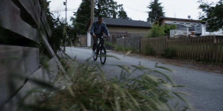 Trevor bikes down the alley.