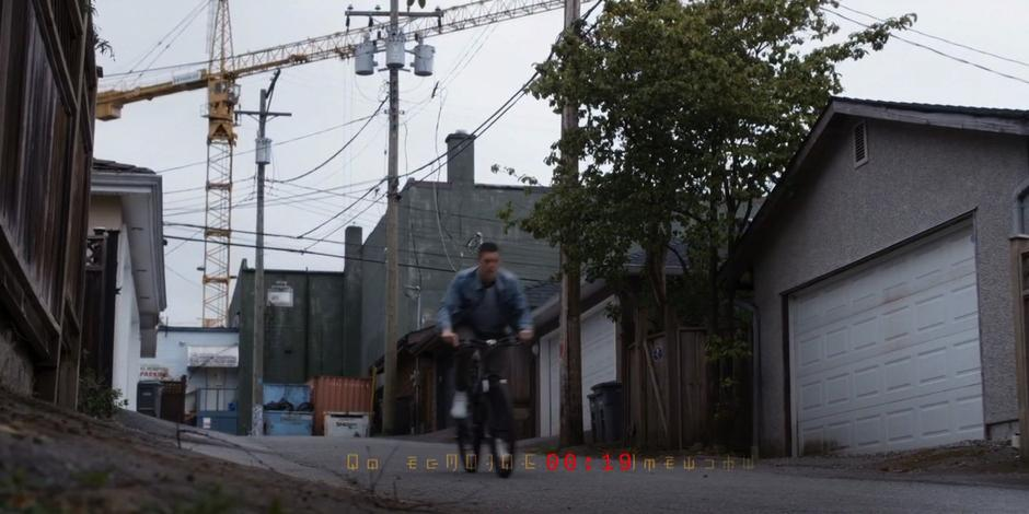 Trevor bikes down another alley with a construction crane in the background as the timer counts down to Kyle's recorded death.