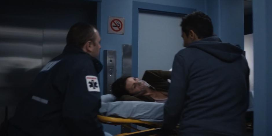 Grant walks with the paramedics as they push Kat into the hospital on a stretcher.