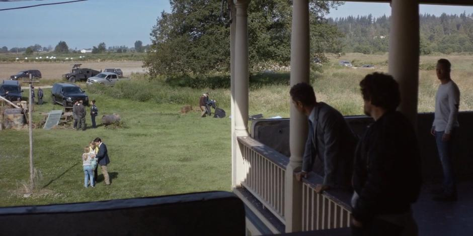 Grant, Rick, and Luca watch from the porch as Anna Hamilton reunites with her parents.
