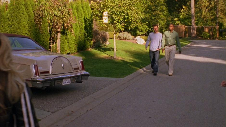 Shawn and Gus walk down the street to Lassiter's house.