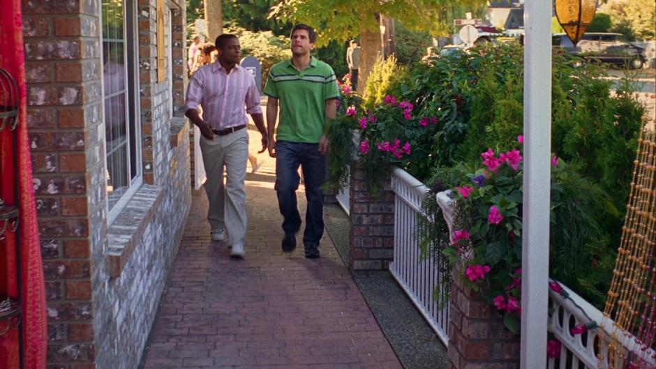 Gus and Shawn walk down the sidewalk to the entrance of the restaurant.