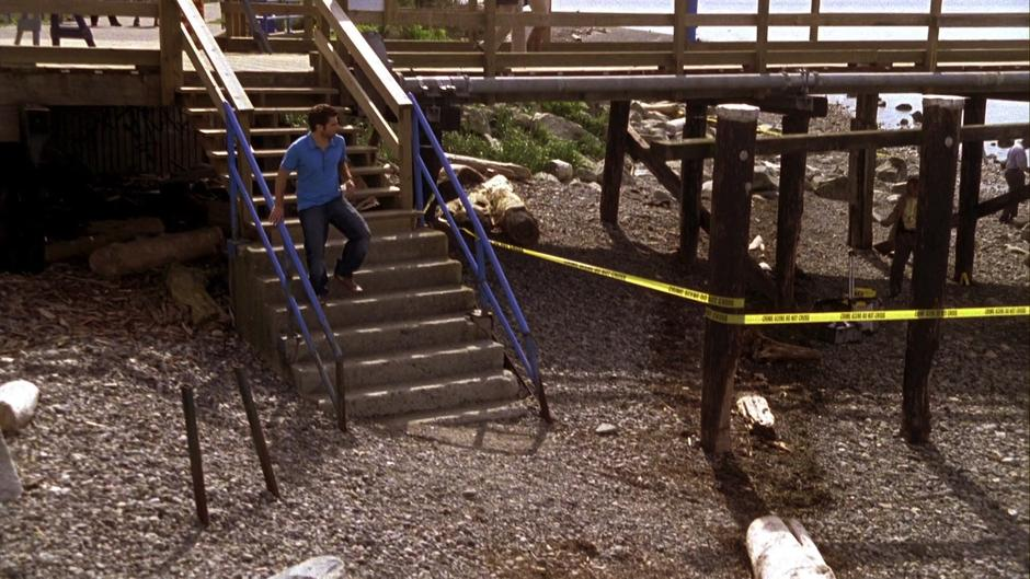 Shawn runs down the stairs to the beach where the crime scene tape is spread.