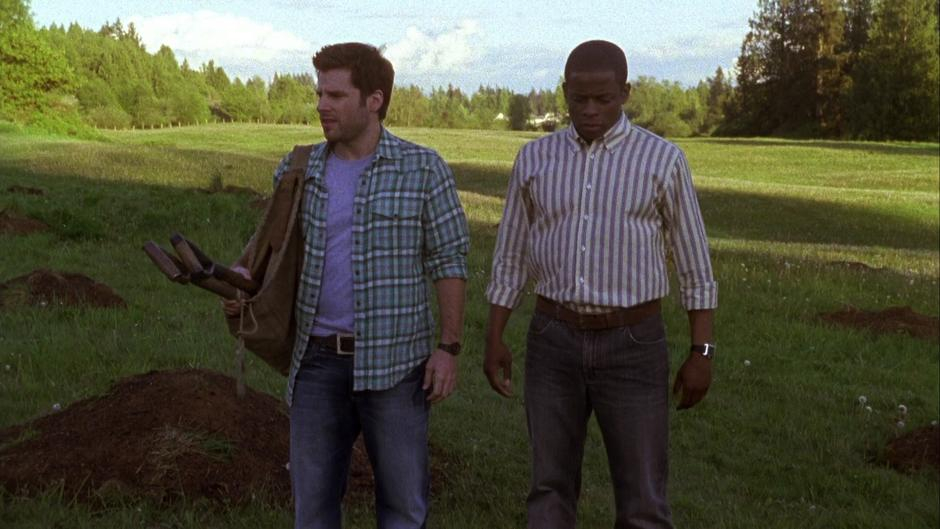 Shawn and Gus return to the field with shovels looking for the correct place to dig.